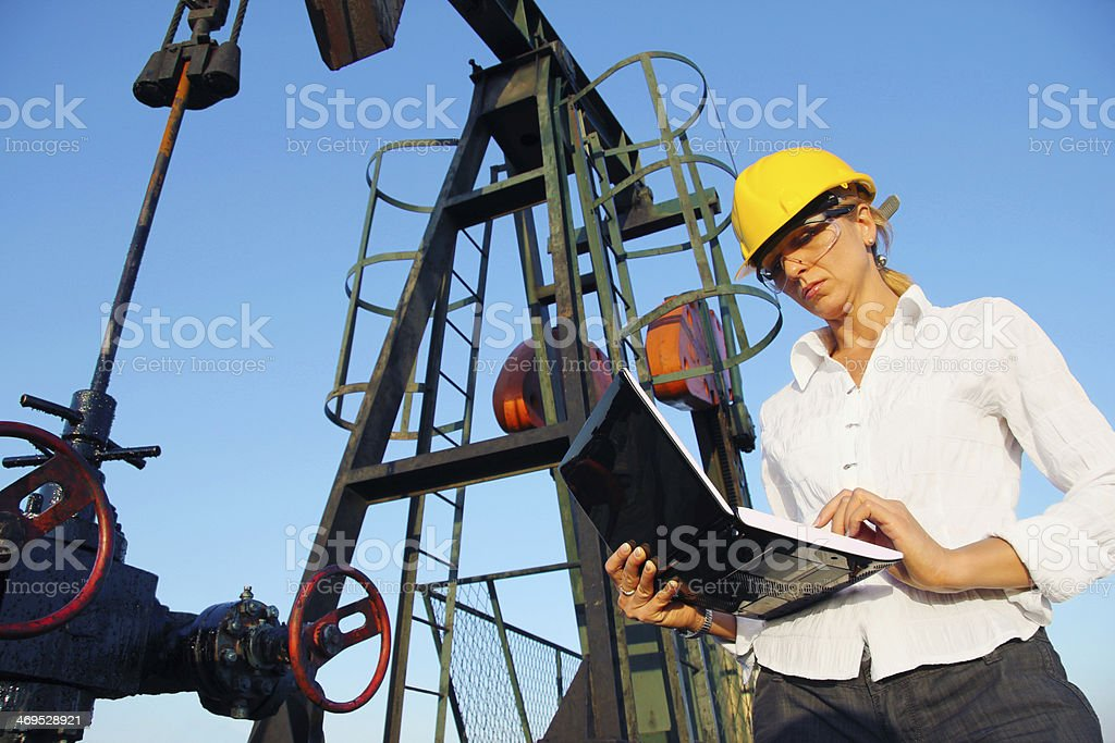 Businesswoman with a notebook in an oilfield stock photo
