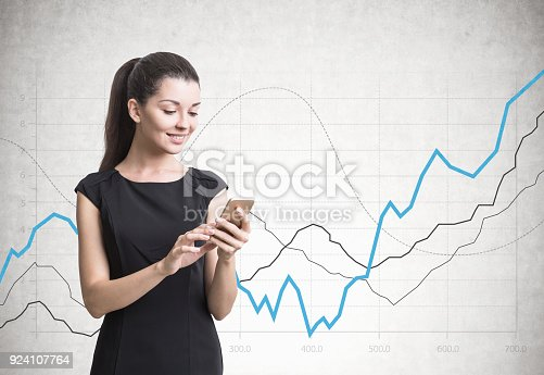 895493084 istock photo Businesswoman with a smartphone, graphs 924107764