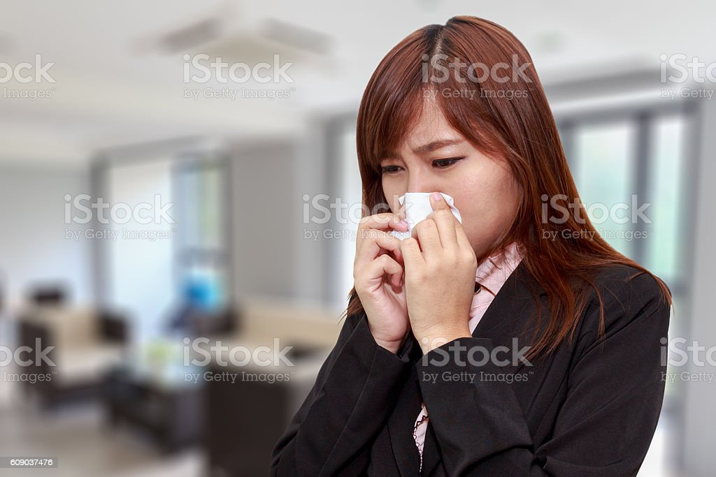 Businesswoman with allergy or cold sneezing into napkin in room stock photo