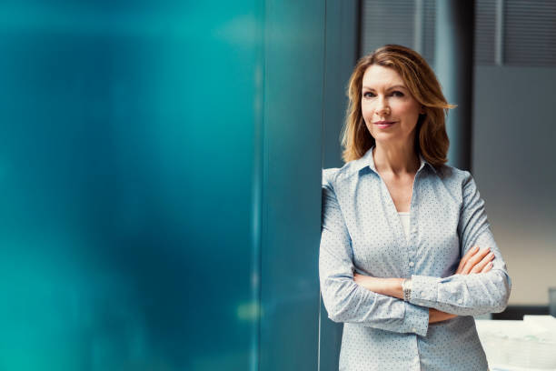 Businesswoman with arms crossed at office stock photo