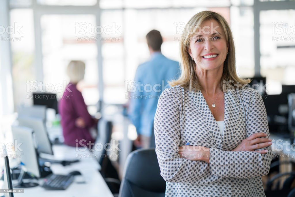 Businesswoman with arms crossed in office stock photo