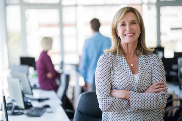businesswoman with arms crossed in office - persona in secondo piano foto e immagini stock