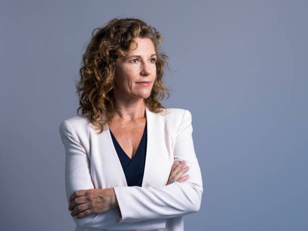 Businesswoman with arms crossed looking away Mature businesswoman looking away against gray background. Confident female executive is contemplating. Manager is standing with arms crossed. looking away stock pictures, royalty-free photos & images