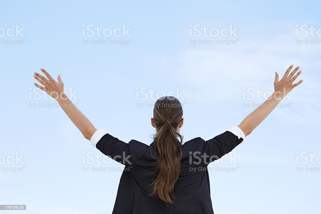 Businesswoman with arms out against blue sky, rear view royalty-free stock photo
