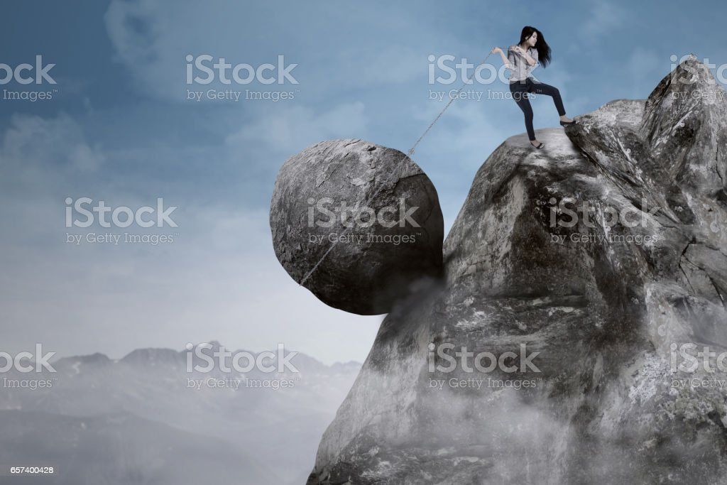 Businesswoman with big rock on the mountain stock photo