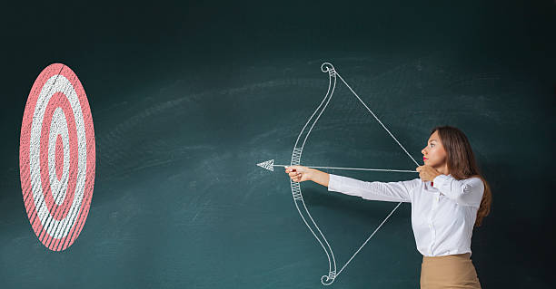 Businesswoman with bow and arrow stock photo