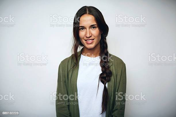 Portrait of businesswoman with braided hair. Confident female professional is wearing jacket. She is smiling over white background.