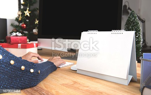 1073023470 istock photo Businesswoman with calendar planner and computer screen in christmas holiday at the office with christmas decoration on table. 1073023464