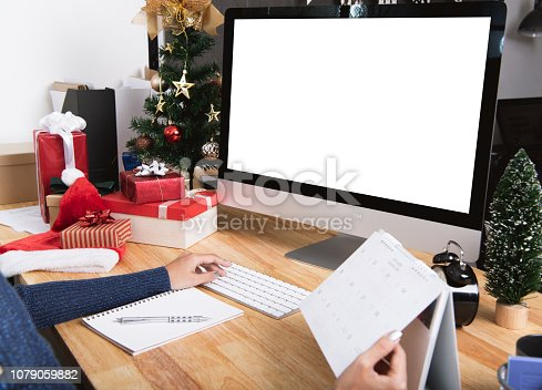 1073023470istockphoto Businesswoman with calendar planner and computer screen in christmas holiday at the office with christmas decoration on table. 1079059882