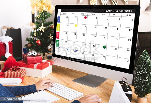istock Businesswoman with calendar planner on computer screen in christmas holiday at the office with christmas decoration on table. 1073023470