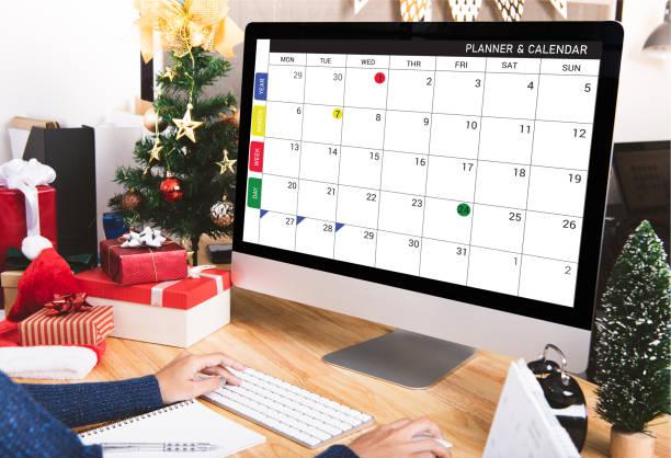 Geschäftsfrau mit Kalender Planer am Computer-Bildschirm in den Weihnachtsferien im Büro mit Weihnachtsdekoration auf Tabelle. – Foto