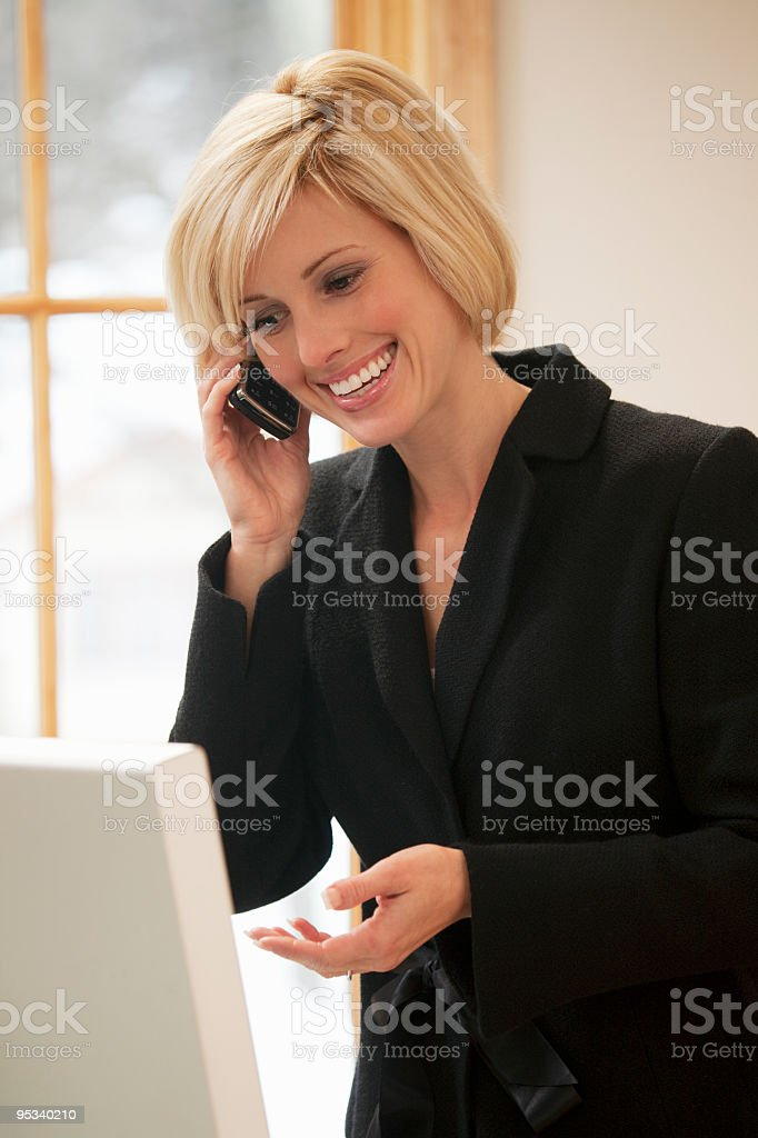 Businesswoman with cell phone and computer royalty-free stock photo