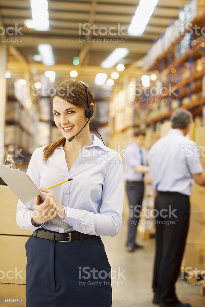 Businesswoman with clipboard working in warehouse royalty-free stock photo