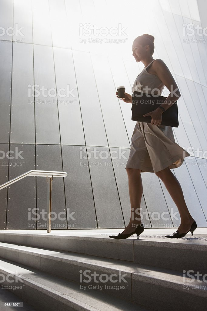 Businesswoman with coffee walking down steps outdoors royalty-free stock photo