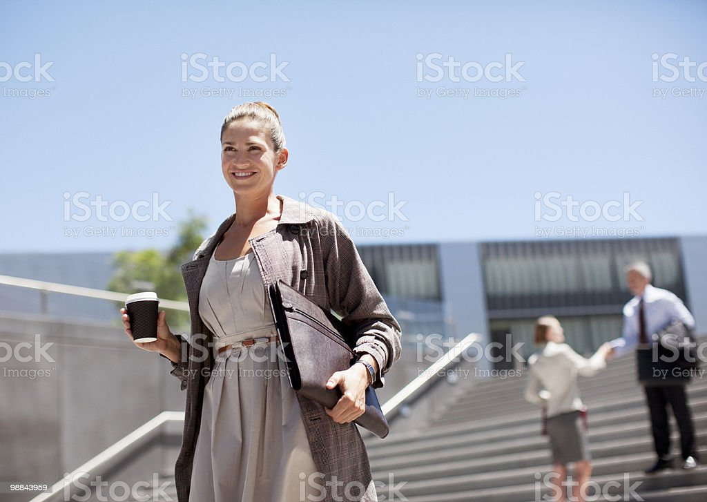 Businesswoman with coffee walking down steps royalty-free stock photo