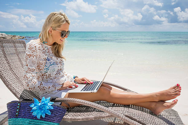 businesswoman with computer on the beach - generic location stock pictures, royalty-free photos & images