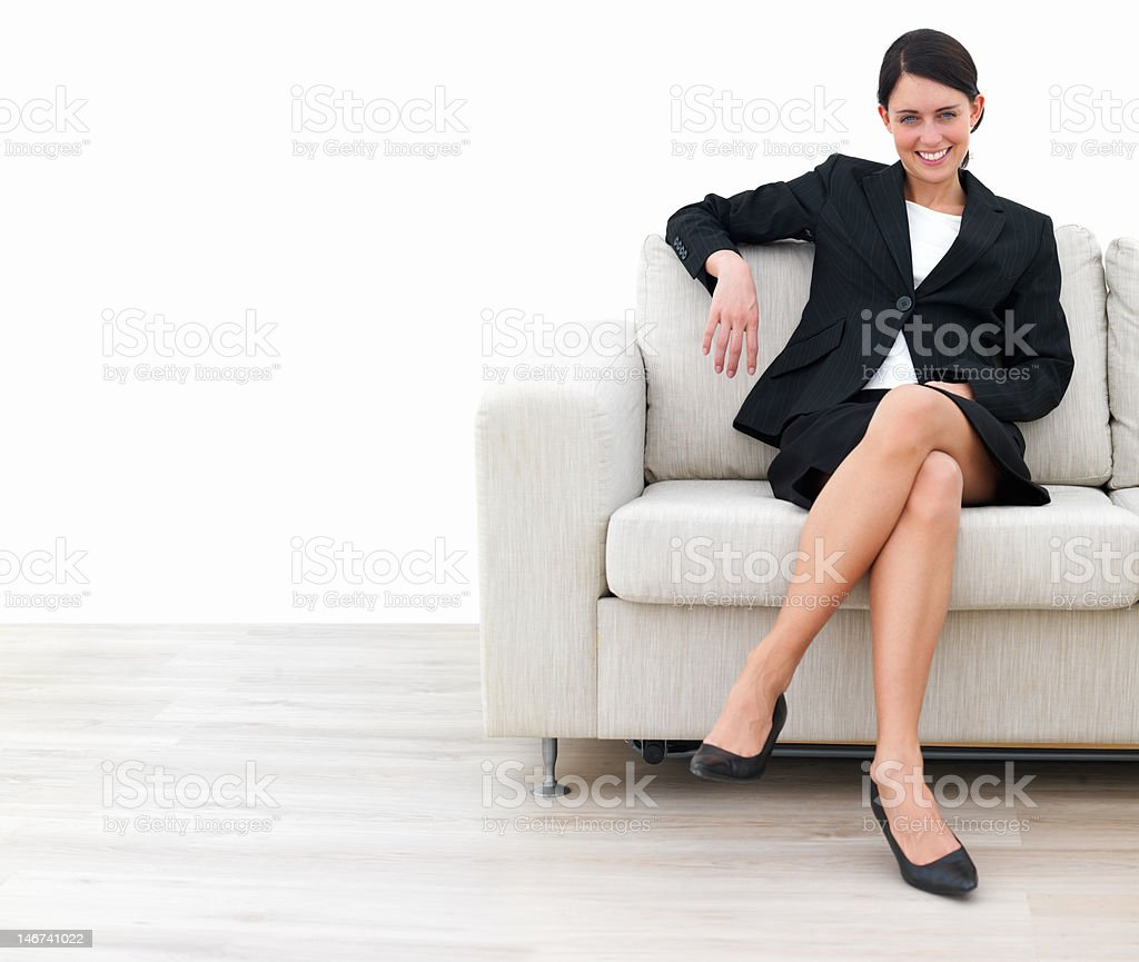 Businesswoman With Crossed Legs Sitting On Sofa Stock