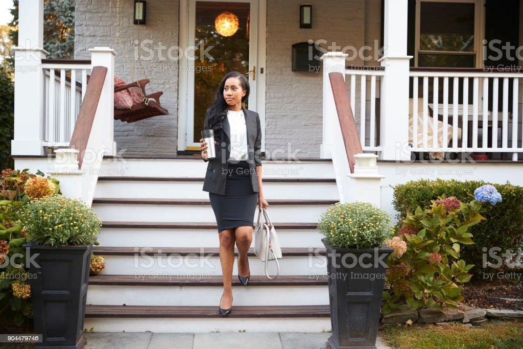 Mulher de negócios com café, deixando a casa de subúrbio para o trabalho - foto de acervo
