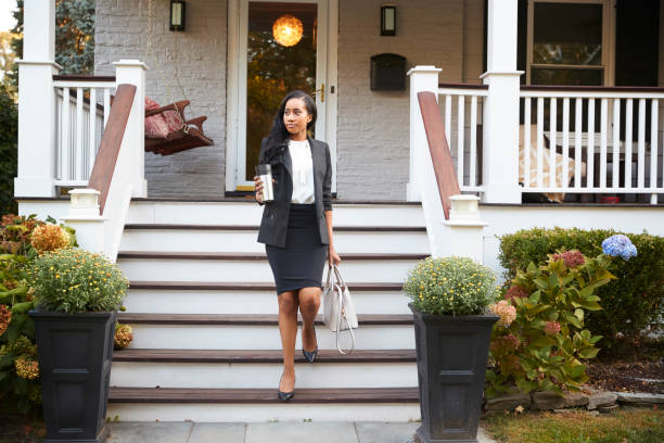 Businesswoman With Cup Of Coffee Leaving Suburban House For Work - foto stock