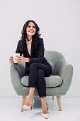 smiling young businesswoman with cup of hot drink sitting in armchair