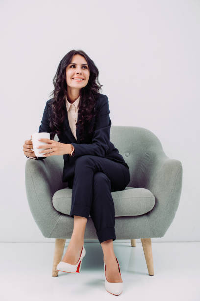 businesswoman with cup of hot drink smiling young businesswoman with cup of hot drink sitting in armchair armchair stock pictures, royalty-free photos & images
