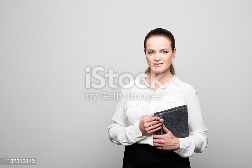 1132314350 istock photo Businesswoman with diary against white background 1132313143