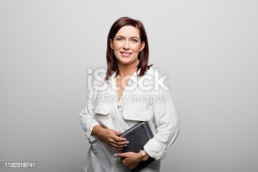 1132314350 istock photo Businesswoman with diary over white background 1132318741