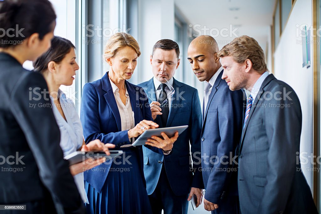Businesswoman with digital tablet and team of associates stock photo