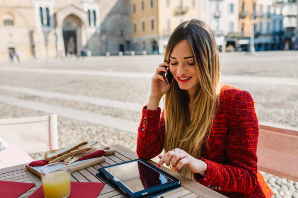 Businesswoman with digital tablet at outdoor cafe stock photo