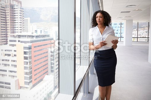 istock Businesswoman With Digital Tablet By Window Of New Office 677893384