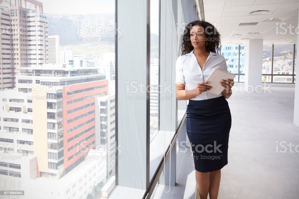 Businesswoman With Digital Tablet By Window Of New Office stock photo