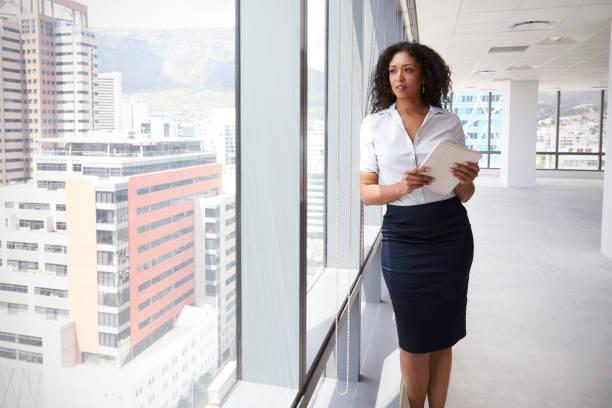 Geschäftsfrau mit digitales Tablet durch Fenster des neuen Büros – Foto