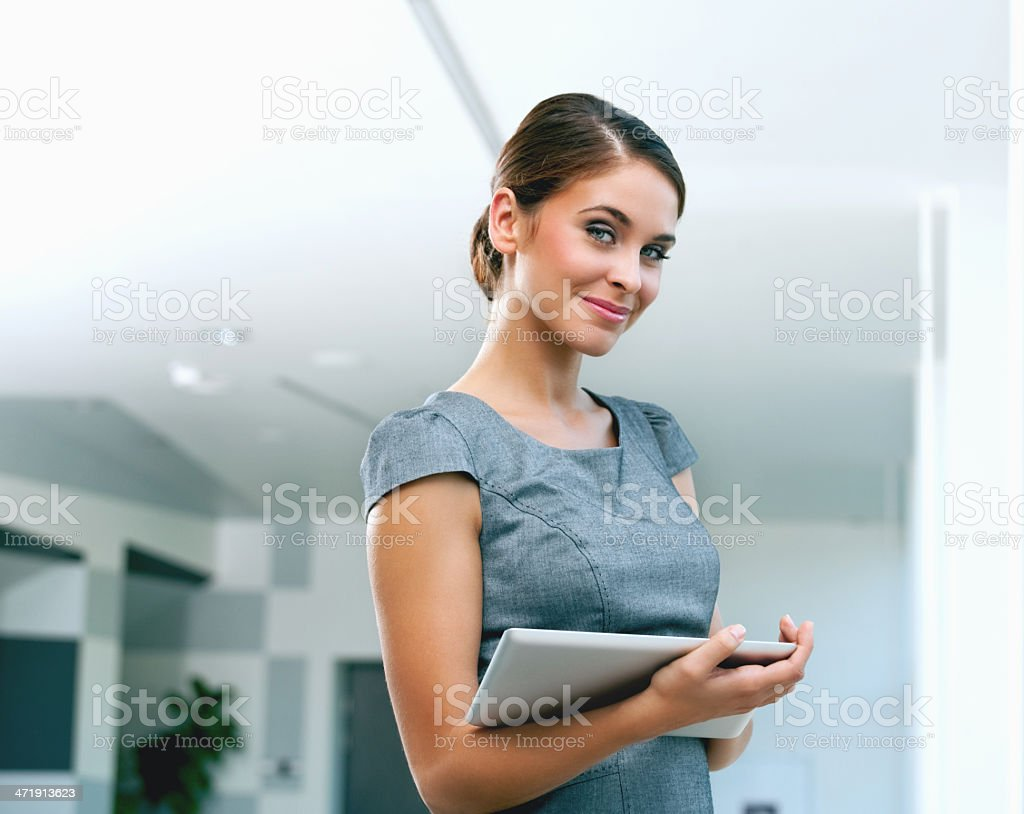 Businesswoman with digital tablet Portrait of an attractive businesswoman holding a digital tablet and smiling at the camera. 25-29 Years Stock Photo