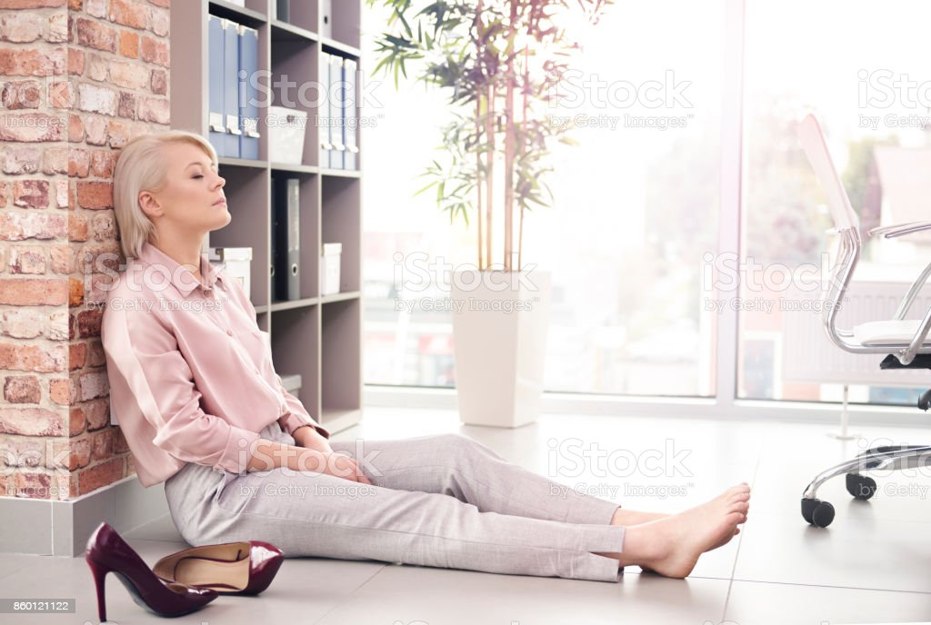 Businesswoman with eyes closed resting on floor стоковое фото