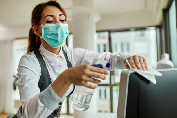 Businesswoman with face mask disinfecting desktop PC in the office. stock photo