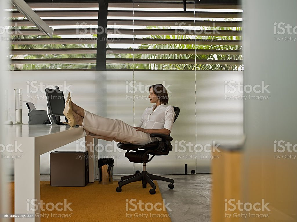 Businesswoman with feet up on desk 免版稅 stock photo
