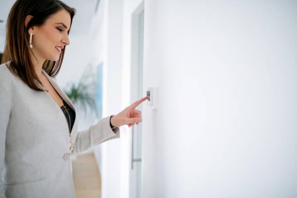 femme d'affaires avec le doigt sur l'interrupteur de lumière - commutateur photos et images de collection