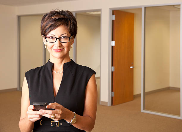 businesswoman with glasses texting stock photo