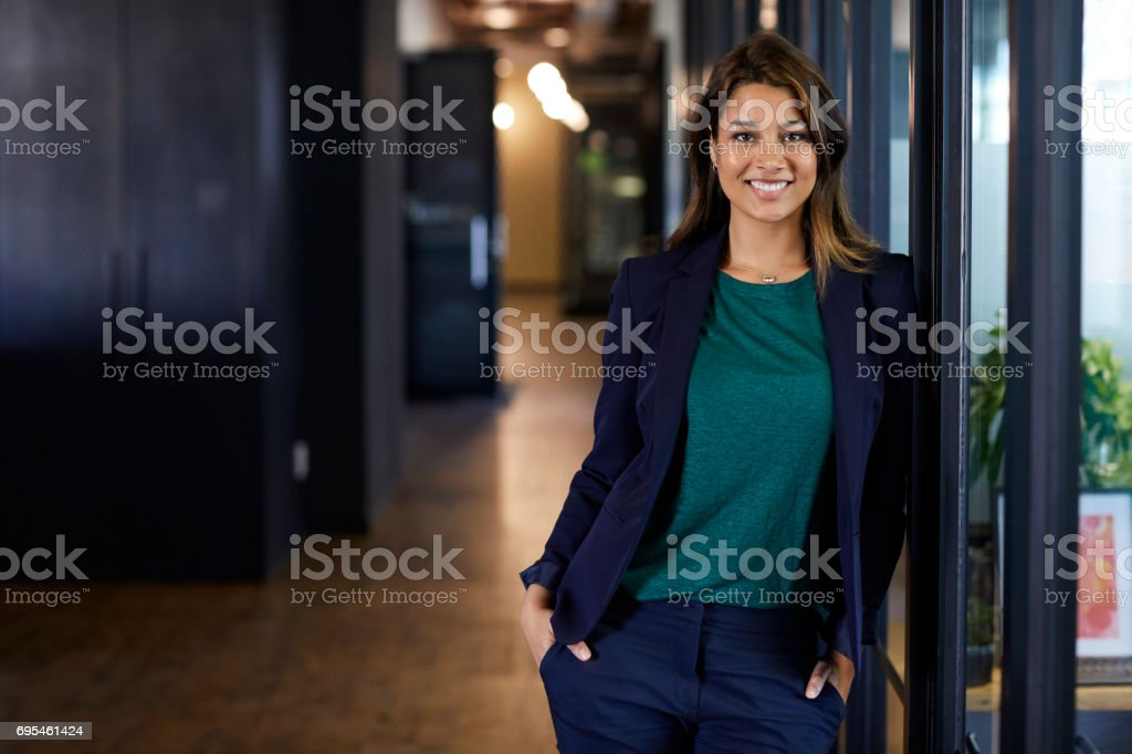 Businesswoman with hands in pockets at office stock photo