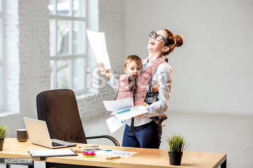 istock Businesswoman with her baby son working with documents at the office 898586996