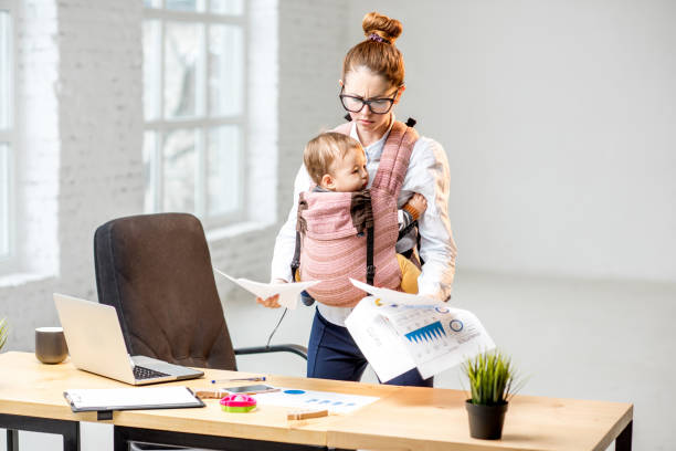 Businesswoman with her baby son working with documents at the office stock photo