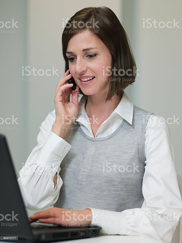 Businesswoman with laptop and cellphone stock photo