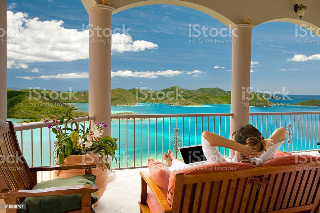 businesswoman with laptop relaxing on her vacation in the Caribbean stock photo