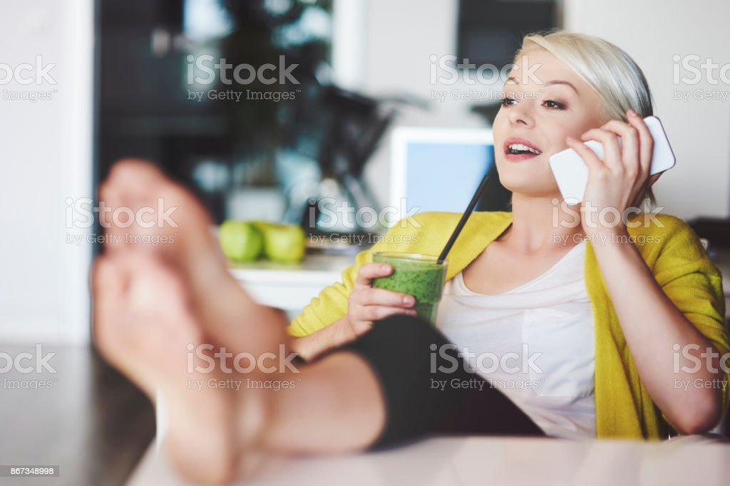 Businesswoman with legs on desk talking by mobilephone стоковое фото