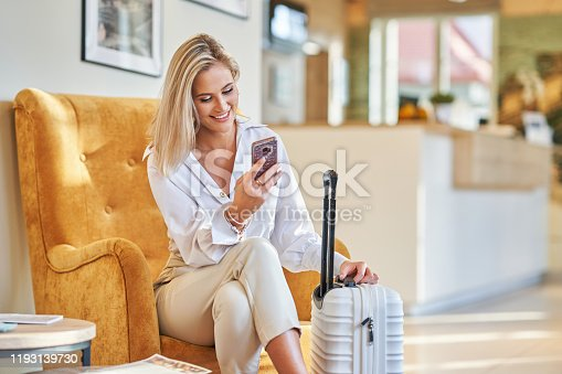 Businesswoman with white suitcase in modern hotel foyer
