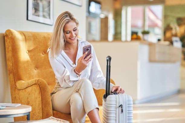 Geschäftsfrau mit Gepäck in moderner Hotellobby mit Smartphone – Foto