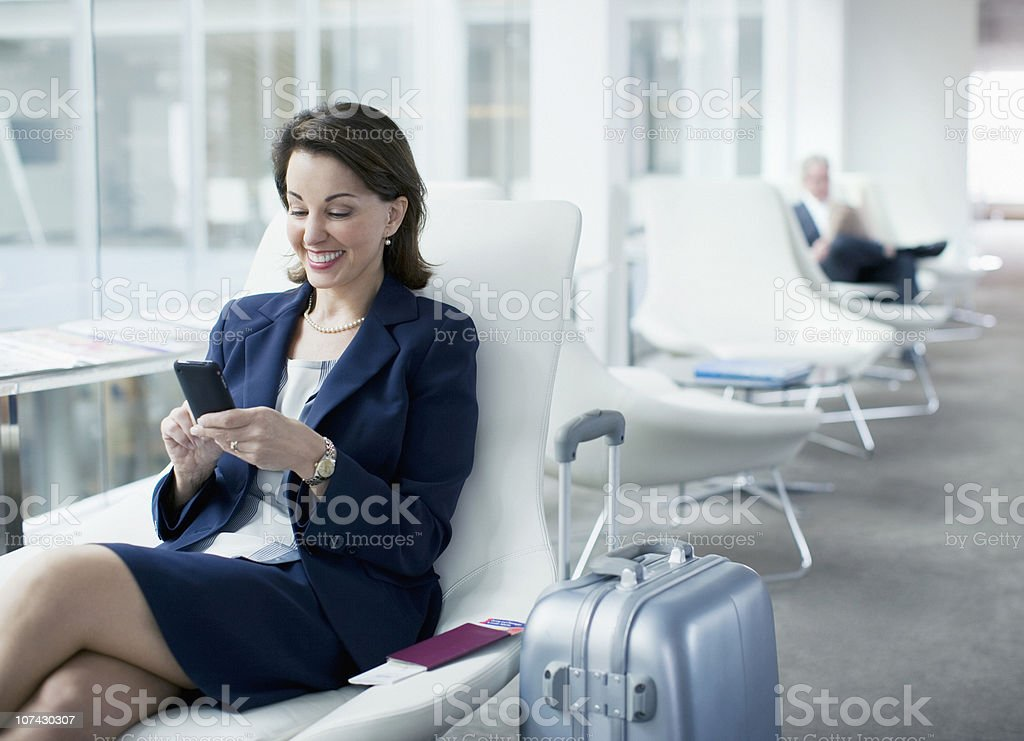 Businesswoman with luggage sitting in airport waiting area stock photo