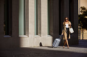 Full length of businesswoman with luggage walking outside airport. Female professional is on business trip. She is walking on street.