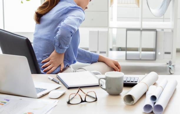geschäftsfrau mit schmerzen im rücken - rückenschmerzen beim sitzen stock-fotos und bilder