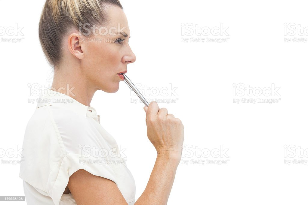 Businesswoman with pen on mouth royalty-free stock photo
